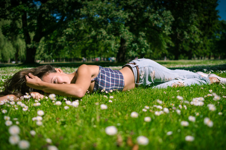 Young joyful woman lies on green grass. Happy girl is relaxing at chamomile field in warm summer day on background of big trees in park. Stock Photo