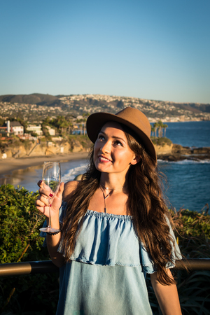 Young beautiful woman in blue dress with wine glass standing on hill and enjoying holidays with amazing view on shore in Laguna beach, California, USA Stock Photo