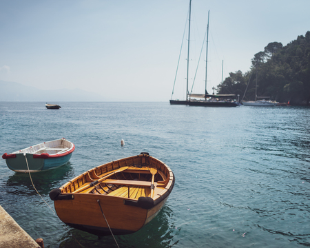 Two wooden fishing boats moored in small marina at Mediterranean village in Italy on background of sailboats and seascape.