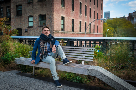 Young elegant man relaxing with view on buildings and trees in High Line park in New York City, USA. Handsome guy sits on bench and looking in camera.