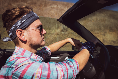 Stylish man in headband and colorful shirt driving cabriolet car, side view. Attractive guy enjoying road trip in summer sunny day in California, USA.