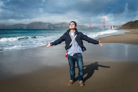 Young man standing on the beach with view on famous bridge in San Francisco, California. Handsome guy gesticulating and enjoying holidays.