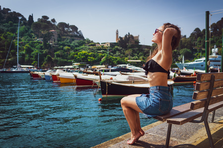 Young barefoot woman sits on bench in marina in Portofino, Italy. Female tourist enjoying sunny day on background of small village, sea and boats.