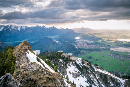 Scenic landscape overlooking snowy mountains and dramatic clouds. Sunlight rays falling on valley with lakes and small villages in Bavaria, Germany.