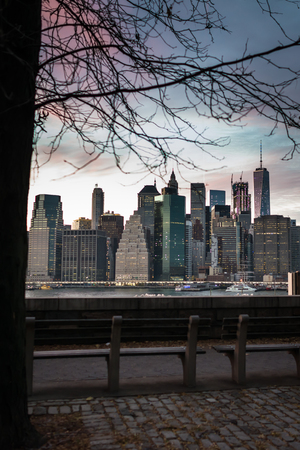 Scenic view from Brooklyn on Manhattan skyscrapers in evening time in New York, USA. Benches on riverside on background of city downtown and sunset.