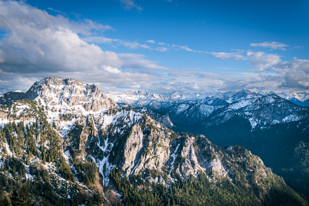 Scenic landscape in Alps overlooking the mountains with forest and snowy tops under dramatic sky in Bavaria, Germany.