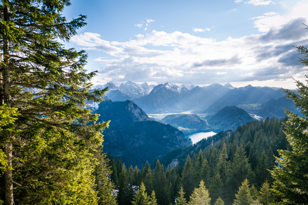 Scenic landscape overlooking the mountains with snowy tops. Sunlight rays falling through the clouds on beautiful valley with lakes and forest.