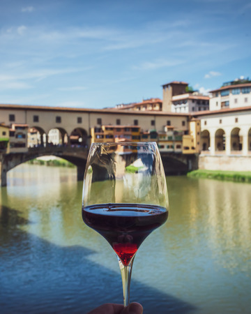 Glass of red wine on background of city and famous bridge in Florence, Italy. View from restaurant terrace on antique buildings in warm summer day.