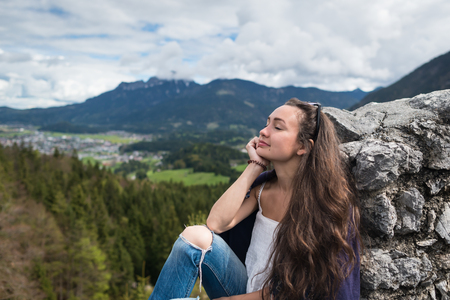 Female traveler sits on peak of mountain with closed eyes on background of valley, forest and village. Young Kazakh girl enjoying day in Alps, Austria Stock Photo