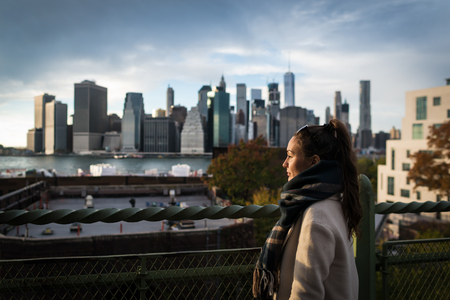Young woman standing on riverside in Brooklyn and looking on Manhattan skyscrapers. Elegant girl on background of city downtown in New York, USA.