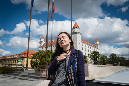 Young woman sits on square with a view on castle. Beautiful girl enjoying holidays on background of main city buildings in Bratislava, Slovakia.