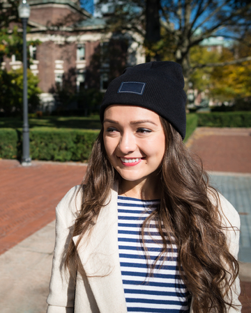 Beautiful young woman stands near buildings of Columbia University in New York, USA. Stylish Kazakh female student smiling on background of campus.