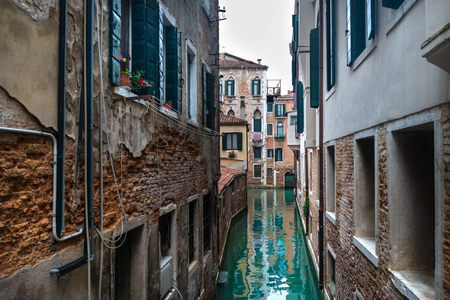 Scenic view on canal in center of Venice, Italy. Vintage houses with brick walls near water and Italian atmosphere in old town. Famous European city.