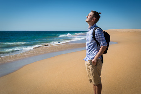 Happy young man in blue shirt with backpack enjoying sunny summer day on the beach in California, USA. Handsome guy standing alone with view on ocean