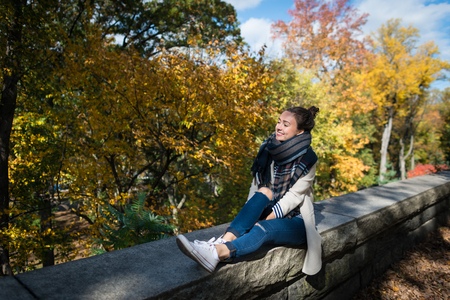 Young smiling woman resting on background of yellow trees and leaves. Happy elegant girl sits alone in park. Sunny autumn day in New York city, USA.