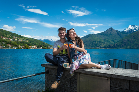 Happy couple sits with two glasses of aperol spritz with scenic view on lake, hills and snowy mountains in Como, Italy. Smiling guy with girlfriend.