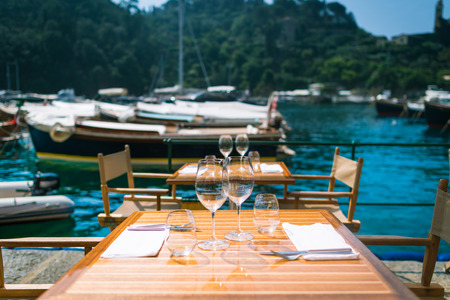 Restaurant with a view in Portofino, Italy. Table serving for dinner with wine glasses on background of marina, small boats and sea in warm summer day