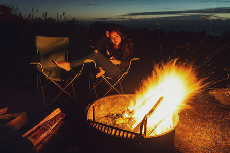 Young thoughtful woman with bottle of beer sits alone near bonfire and firewood in the evening. Barefoot sadness girl looking on bright fire in dark. Stock Photo