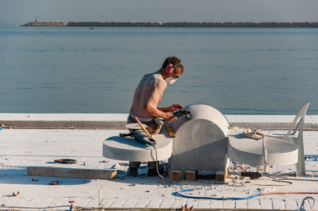 Mersin, Mezitli  Turkey - 11 15 2010: Unknown sculptor carves sculpture from white marble with grinding tool. Sea in the background. Editorial
