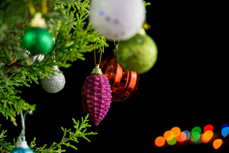 Christmas ornaments on pine tree branches. Colorful bokeh on black background.