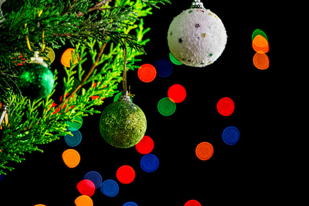 Christmas balls hanging on Christmas tree branches. Colorful bokeh on black background.