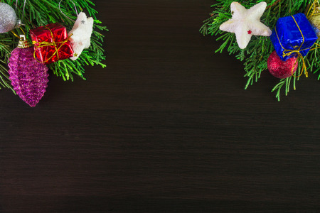 Christmas ornaments and pine tree branches on corner of wooden background. Brown blank aerial;
