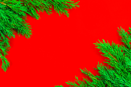 Corner of frame with Christmas tree branches on red background for Christmas decoration. Red blank aerial.