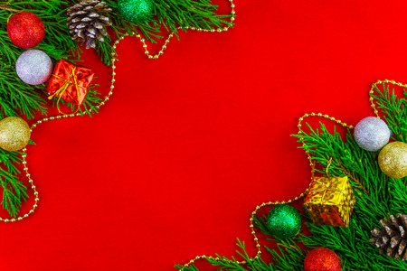 Corner of frame with Christmas tree branches and christmas ornaments on red background for Christmas decoration. Red blank aerial.
