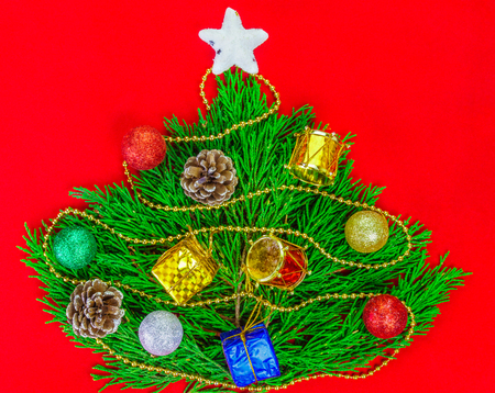 Christmas ornaments and top of star on miniature pine tree design on red background for Christmas decoration.