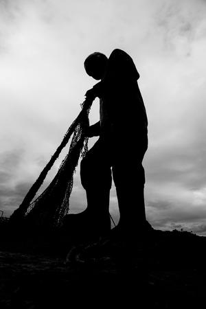 Black and white fisherman statue, Dramatic silhouette artwork. Izmir, Turkey.