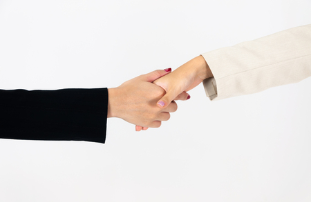 Two businesswomen shaking hands, white background. Teamwork concept