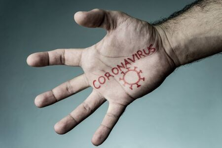 Coronavirus text written on hand of man. Covid-19, Coronavirus, SARS-CoV-2 outbreak. 2019 Novel Coronavirus concept and background. 版權商用圖片