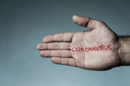 Coronavirus text written on hand of man. Covid-19, Coronavirus, SARS-CoV-2 outbreak. 2019 Novel Coronavirus concept and blue background.
