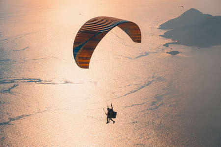 Paragliding in the sky. Paraglider tandem flying over the sea with mountains at sunset. Aerial view of paraglider and Blue Lagoon in Oludeniz, Mugla, Turkey.
