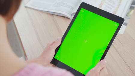 Working with a tablet computer: a green screen and a tablet in the hands of a young woman. It touches the screen, mimics the flipping. Taken over the shoulder, only the tablet and hands in the frame.