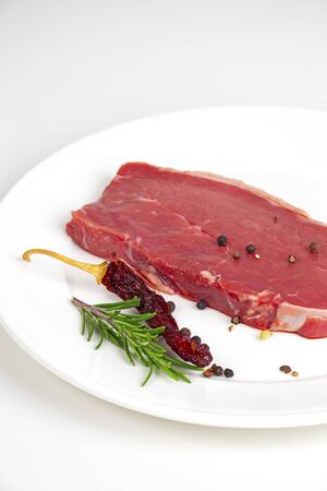 raw beef steak with red pepper