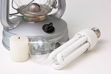 candle, a kerosene lamp, and electric lamps photo