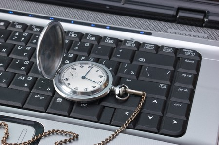 pocket watch on a laptop keyboard Stock Photo - 7242705