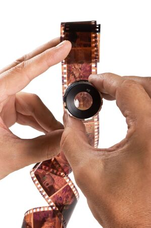 celluloid film: hand holding a magnifying glass and twisted film