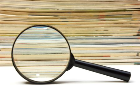 magnifier on the background of the stack of magazines photo
