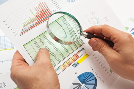 magnifying glass in hand and working paper chart