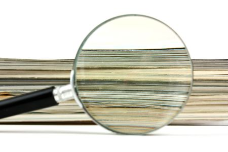 stack of papers: magnifying glass and a stack of magazines Stock Photo