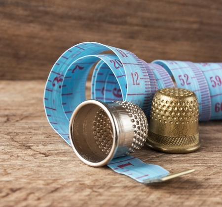 two thimble and measuring tape on a wooden background