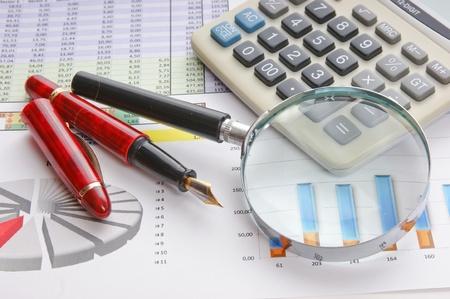 financial leadership: Pluma, lupa y el documento de trabajo con un diagrama