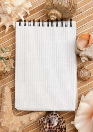notebook on the background of mats and sea shells photo