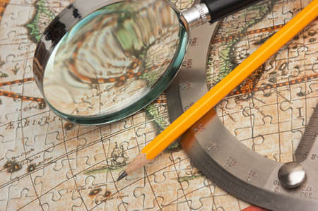 old map and a loop with a protractor, still life photo