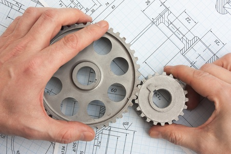 technical drawing and pinion gears in hands Stock Photo