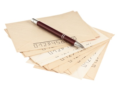stack of mail envelopes and a pen isolated on white background photo