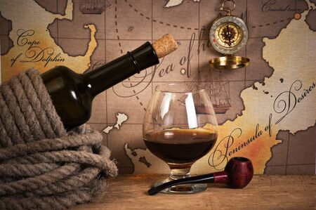 vintage world map: bottle and  glass of wine on background of old maps