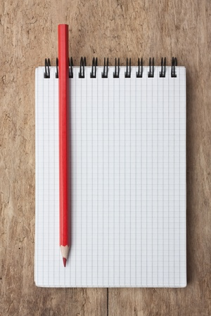 r image: red pencils and notebook on a wooden background